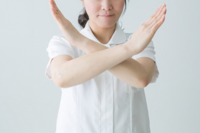 手でバツを作る女性